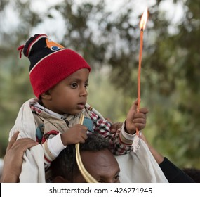 LALIBELA, ETHIOPIA - 08 JANUARY 2016: An ethiopian boy sits on his father's shoulders holding a candle near the Bet Maryam church during the ethiopian orthodox Christmas celebrations.