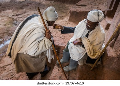 LALIBELA, ETHIOPIA - AUGUST 24, 2015: unidentified worshipper kiss the Holy Cross in front of a rock church. Lalibela churches were carved from the rock in the X th sec and still are center of worship