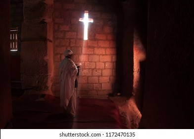 Lalibela, Ethiopia, January, 2018.  Christian Monk in traditional ethiopian dress praying in rock-hewn church on orthodox Christmas eve