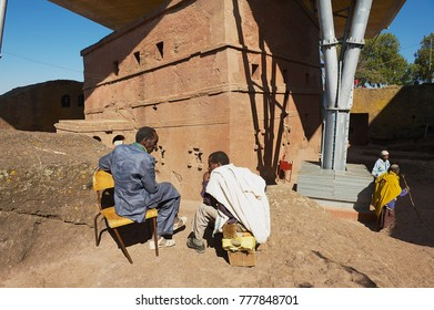 LALIBELA, ETHIOPIA - JANUARY 27, 2010: Unidentified pilgrims talk with the monolithic rock-hewn church at the background in Lalibela, Ethiopia.