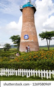 Lam Dong, Vietnam - Sep 8, 2018: A Vietnamese family taking memorial photo with a windmill on Vinamilk organic farm. Vinamilk is the biggest giant in milk industry in Vietnam.