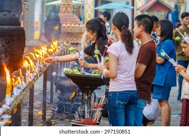 LAM POON, THAILAND-APRIL 15 : Songkran Day. Traditional buddhist people are lighting candles for religious ceremonies at Wat Phra That Hariphunchai temple.on April15, 2008 in Lam poon,Thailand