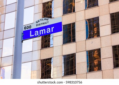 Lamar street sign in downtown Houston, Texas with a skyscraper in the background.