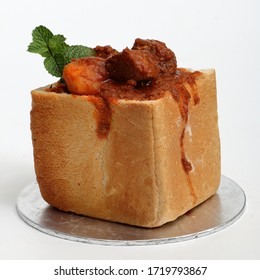 """A lamb """"bunny chow"""" - the popular, Indian fast food cuisine which originated in South Africa. Consists of lamb curry in a hollowed-out loaf of white bread. Garnished with fresh mint. Square format."""