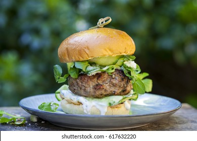 Lamb burger with pickled cucumber, fresh salad leaves and mint and garlic yogurt