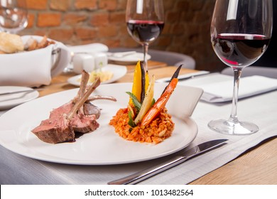 Lamb chops, braised lentils with mint, roast vegetables and rosemary sauce served in a restaurant