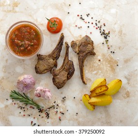 Lamb chops grilled. Tartar sauce, tomato and fried potatoes with rosemary, garlic and spices. Food cooked mutton with herb for dinner. Cooked meat with spices. Top view
