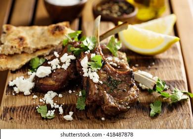 Lamb chops with herbs, lemon, pita bread and feta