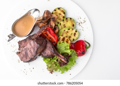 Lamb chops on bone. Roasted Rectangle Rack of Lamb Chops with grilled vegetables.