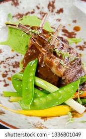 Lamb chops with snow pea, carrot, asparagus, leek and pea mash on a black background