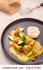 Lamb curry with currysauce courgettes and tomatoes on a black plate