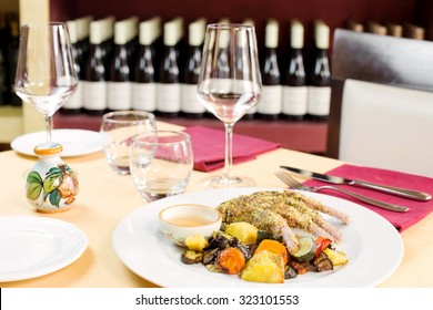 lamb cutlet cooked with pistachio crust and grilled vegetables over restaurant table background