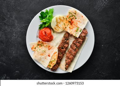 Lamb Kebab. Pita bread and spices. On a black background. Top view.