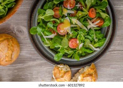 Lamb lettuce salad with dijon dressing, crispy bun and parmesan cheese on top