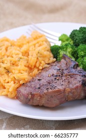 Lamb loin chop dinner with a side of cheddar rice and steamed broccoli