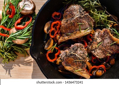 Lamb loin chops on cast iron pan with rosemary and paprikas on the side.