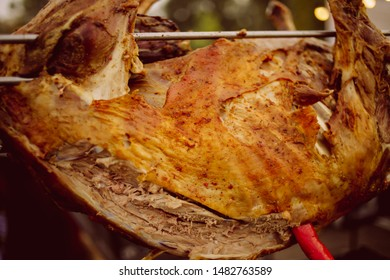 lamb on a spit. Whole lambs baked on a spit, direct on fire outdoor. Spit-roasted meat. Traditional Caucasian cuisine. Smoked meat in the smoke and on an open fire. vintage photo processing