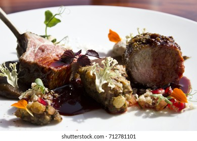 Lamb rack with cauliflower, aubergine, curd cheese, dates and hibiscus on white plate side view