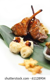 Lamb rack with eel mashed potato served on banana leaf placed on white background