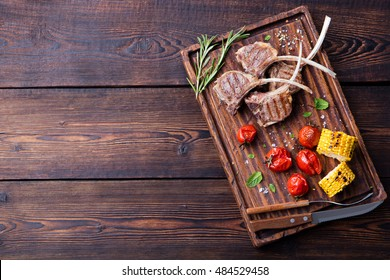 Lamb ribs grilled on cutting board with roasted vegetables. Top view Copy space Wooden background.