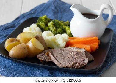 Lamb roast Sunday lunch dinner with vegetables on a aquare black plate, with gravy jug, on a blue tea towel.  White wood background