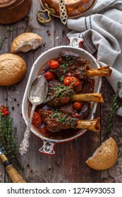 Lamb shanks in rich tomato sauce with bread and herbs, top view