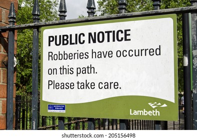 LAMBETH, UK - MAY 24, 2014:  A sign fixed to the gate to Kennington Park in Lambeth, South London, warning pedestrians of the threat of robbery in the area.