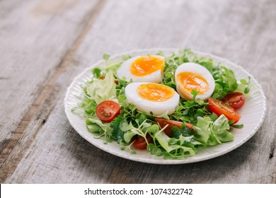 Lambs lettuce salad, hard-boiled eggs, tomatoes and honey mustard dressing