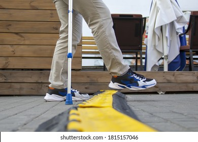 A lame man with an elbow crutch steps over a cable channel in the street.