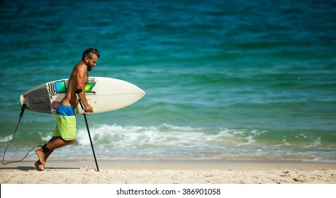 Lame man in swimsuit going in water with surfboard