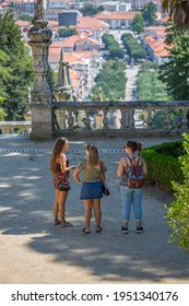Lamego Portugal - 07 25 2019 : View of three young girls talking in the stairs of Lamego Cathedral, Lamego city downtown as background