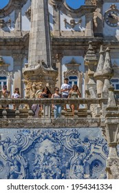 Lamego Portugal - 07 25 2019 : View of tourists walking down stairs of Lamego Cathedral, ceramic tile panel and pinnacles, Cathedral as background