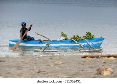 Lamen Bay, Epi island, Vanuatu-October 4, 2016: Local boy on his dugout rowboat with outrigger transports some banana bunches across the bay to sell them in the market. Lamen Bay-Epi island-Vanuatu.