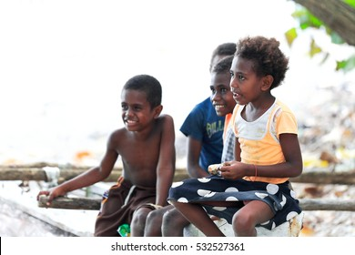 Lamen Bay, Epi island, Vanuatu-October 4, 2014: Four kids of the Ni-Vanuatu people take a rest to chat with the tourists after coming back from school while sitting on a fence waiting for lunch time.