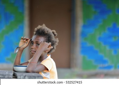 Lamen Bay, Epi island, Vanuatu-October 4, 2014: Young girl of the Ni-Vanuatu people unwillingly has lunch sitting at an outdoor table in front of her house after having arrived from school at midday.