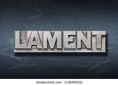 lament word made from metallic letterpress on dark jeans background