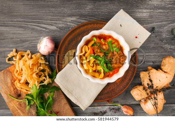 Lamian (lagman) - traditional asian noodles soup with meat, vegetables, herbs, spices and meat broth served on wooden table with ingredients (noodles, parsley, garlic, ginger, cilantro).