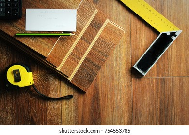 Laminate floor planks and tools on wooden background. Different carpenter tools on the laminated floor .Top view