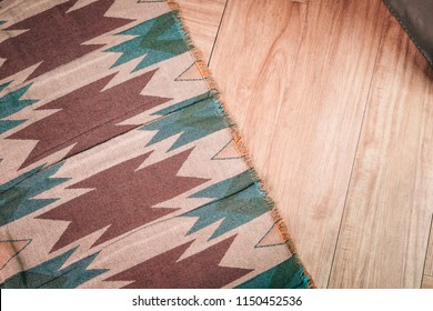 Laminate parquete floor. Light wooden texture. Thin aztec, mexican style print carpet. Minimalism interior design concept