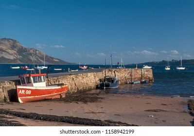Lamlash Arran Scotland UK 09/01/1999: Fishing boats at harbour wall with Holy Isle in background
