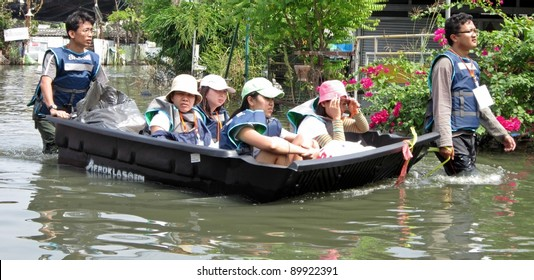 LAMLUKKA (PATHUMTHANI), THAILAND – CIRCA NOVEMBER 2011 – An unidentified rescue team pushes a boat that transports a group of unidentified people through a flooded road circa November 2011 in Lamlukka