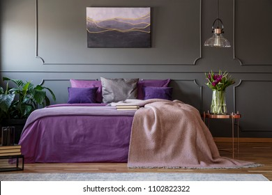 Lamp above copper table with flowers next to bed with violet bedding in purple bedroom interior
