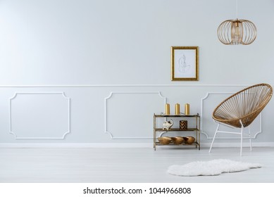 Lamp above gold chair and white fur in sophisticated living room interior with poster and copy space