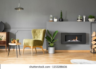 Lamp above green armchair and table in grey apartment interior with plant and fireplace. Real photo