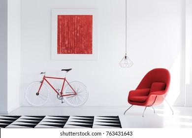Lamp above red armchair in bright interior with black and white carpet and red painting on the wall above bike