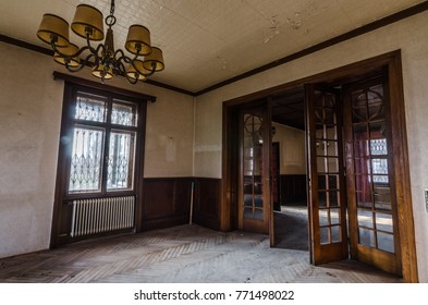 lamp and big wooden door in anteroom of abandoned house