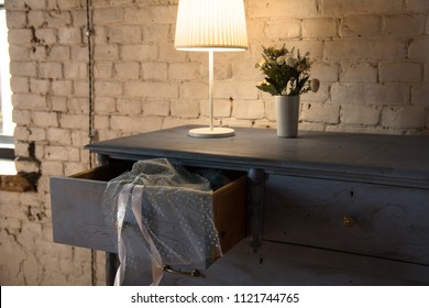 Lamp and bouquet with flowers on an old chest of drawers background brick wall. Clear chest of drawers with a transparent cloth