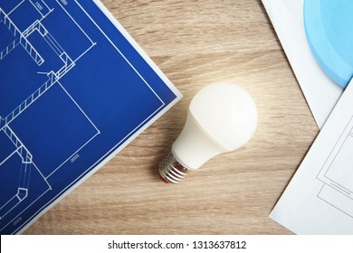 Lamp bulb and blueprint on wooden table, top view