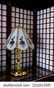 Lamp with a decorative lampshade on a bedside table with a divider background.