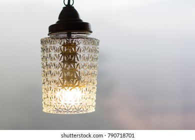 The lamp with incandescent bulb. The  beautiful lamp and bulb with strong fog behind.